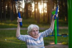 An elderly woman doing morning exercise on the street sport playground.  Sport. Stock Images