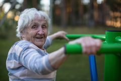 An elderly happy woman doing morning exercise on the street sport playground. Royalty Free Stock Image