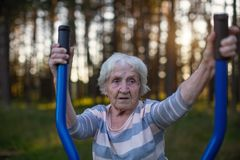 Elderly woman doing morning exercise on the street sport playground. Sport. Stock Photo