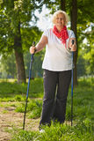 Elderly woman doing nordic walking in forest Stock Photo