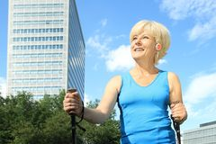 Elderly woman doing nordic walking outdoor Royalty Free Stock Images