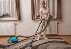 Elderly woman doing woman chores at home. Vacumming the carpet stock photos