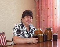Elderly woman with domestic purveyances Stock Photos