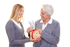 Elderly woman donating money. Grandmother putting money in piggy bank of her granddaughter Stock Images