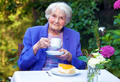 Elderly Woman Drinking Coffee at the Garden Table Royalty Free Stock Image