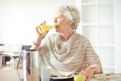 Elderly Woman Drinking Juice stock images