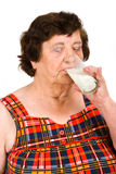 Elderly woman drinking milk stock image