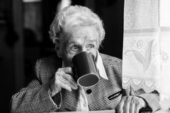 Elderly woman drinking tea. Black-and-white photo Stock Image
