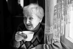 Elderly woman drinking tea. Happy. Elderly woman drinking tea. Black and white photo Stock Image