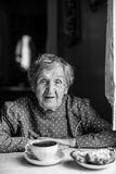 Elderly woman drinking tea in the house in the village. Royalty Free Stock Images