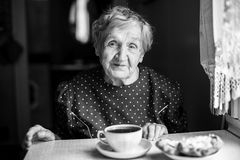 Elderly woman drinking tea in the kitchen. Elderly woman drinking tea in the kitchen, black and white portrait of grandmother Royalty Free Stock Image