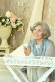Elderly woman drinking tea Stock Photography
