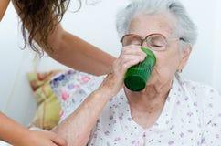Elderly woman drinking water Stock Photos
