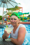 Elderly woman drinks mojito in swimming pool Royalty Free Stock Photos