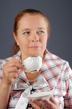 The elderly woman drinks tea. Stock Image