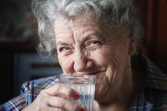 Smile elderly woman drinks water. Elderly woman drinks water on a dark and black background Royalty Free Stock Image