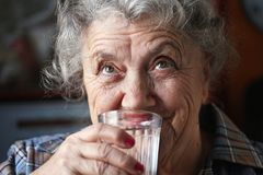 Smile elderly woman drinks water. Elderly woman drinks water on a dark and black background Stock Image