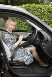 Elderly woman driver fastening self belt in a car Royalty Free Stock Image