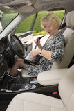 Elderly woman driver fastening self belt in a car Stock Photos