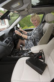Elderly woman driver with handbag about to set off Stock Image