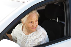 Elderly woman driving car. Attentive elderly woman driving car Stock Images
