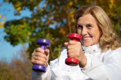 Elderly woman with dumb bells Stock Image