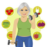 Elderly woman with dumbbells and variety of healthy vegetables Stock Photo