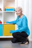 Elderly woman dusting shelves. Smiley elderly woman dusting shelves at home Royalty Free Stock Photo