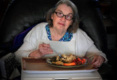 Elderly woman eating dinner Royalty Free Stock Image
