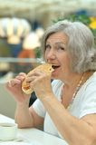 Elderly woman eating fast food Stock Image