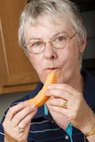 Elderly woman eating fresh cantaloupe Royalty Free Stock Photo