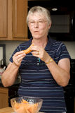 Elderly woman eating fresh cantaloupe Royalty Free Stock Photos