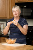 Elderly woman eating fresh cantaloupe Stock Images