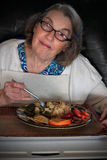 Elderly woman eating lunch Royalty Free Stock Image