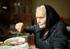 Elderly woman eating soup. Old rural woman eating her soup from a bowl Stock Photo
