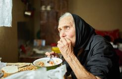 Elderly woman eating soup. Old rural woman eating her soup from a bowl Royalty Free Stock Photos