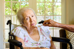 Elderly woman. Elderly eighty plus year old woman in a wheel chair being fed in a home setting Royalty Free Stock Image