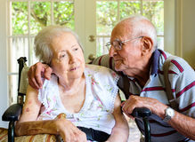 Elderly woman. Elderly eighty plus year old women in a wheel chair in a home setting with her husband Royalty Free Stock Image