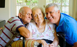 Elderly woman. Elderly eighty plus year old women in a wheel chair in a home setting with her husband and son Royalty Free Stock Image