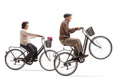 Elderly woman and an elderly man riding bicycles with the elderl. Elderly women and an elderly men riding bicycles with the elderly men doing a wheelie isolated royalty free stock images