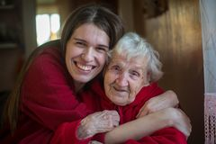 An elderly woman in an embrace with his adult daughter. Royalty Free Stock Photos