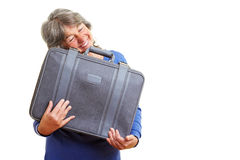 Elderly woman embracing suitcase Royalty Free Stock Images
