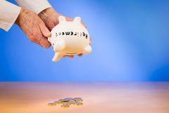 Elderly woman empties her piggybank  with savings retirement Stock Photo