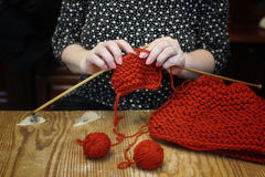 Elderly woman is engaged in knitting warm sweaters for her grand Stock Photography