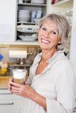 Elderly woman enjoying a cup of cappuccino Stock Images