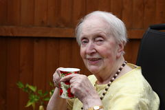 Elderly woman enjoying drink. An 84 year old woman smiles into the camera while enjoying a drink of coffee royalty free stock photos