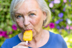Elderly woman enjoying a refreshing iced lolly. Attractive blond elderly woman enjoying a refreshing iced orange fruit lolly outdoors on a hot summer day looking Stock Image