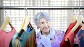 Elderly woman enjoys shopping in a second-hand shop. Elderly woman is not wealthy therefore she likes shopping second-hand shop stock video footage