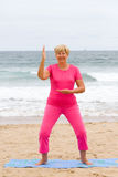 Elderly woman exercise. Happy elderly woman doing fitness woman exercise on beach royalty free stock image