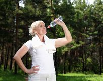 Elderly woman after exercising in the forest Stock Photography